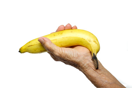 Old woman hand with banana isolated on white