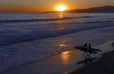 夕日とビーチで海の上のサーフ 写真素材