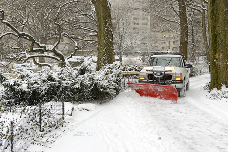 Truck with plow snowplowing road after snowstorm Stock Photo