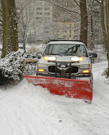 blustery: Truck with plow snowplowing road after snowstorm Stock Photo