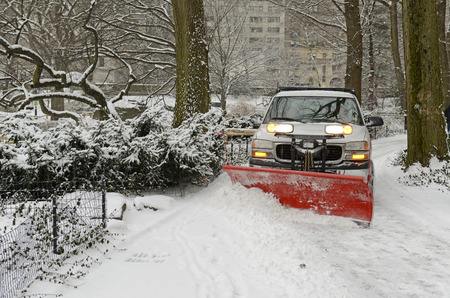 Truck with plow snowplowing road after snowstorm Foto de archivo