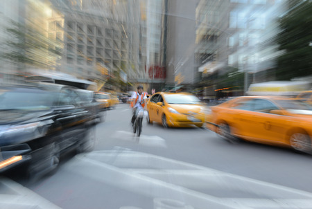 purposely: Purposely Blurred taxi cabs and vehicles in traffic showing fast motion concept in urban setting, Manhattan, New York.