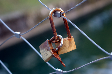Macro photo of rusty keys and locks clinging to one another on a metallic bridge fence in the center Banco de Imagens