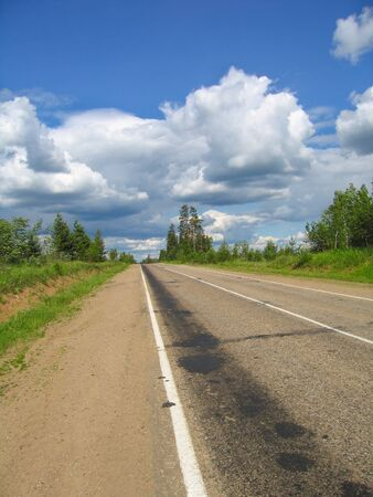 The road stretches into the distance, trail braking on the road Stock Photo