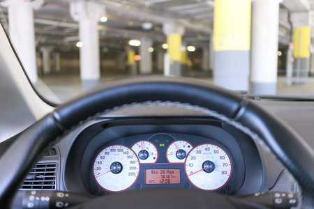 instrumentation: Close up of a steering wheel and instrumentation of a car the background in the parking lot of a mall. Stock Photo