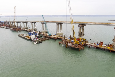 Construction of the bridge. Engineering facilities for the construction of a railway and automobile bridge across the strait. Stock Photo