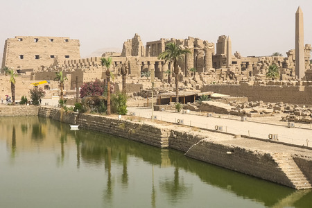 A pond near the ancient Egyptian buildings and ruins.