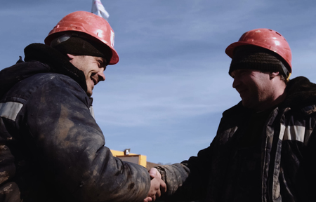 Irkutsk, Russia - March 24, 2017: Two builder oilmen greeted each other. Working greeting.