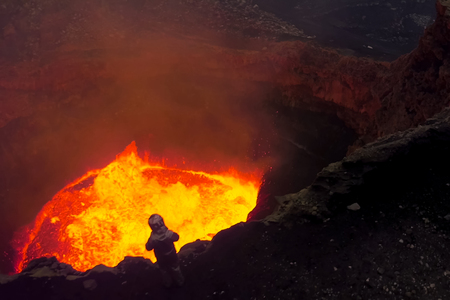 A man in a protective suit near the mouth of the volcano. Investigation of the volcano.
