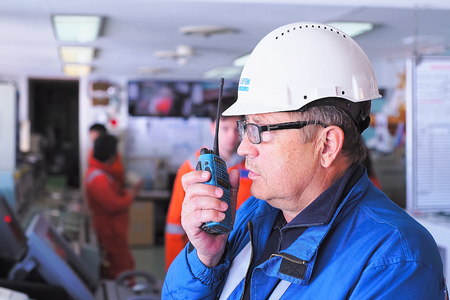 Sea of Okhotsk near Sakhalin, Russia - July 26, 2017: The companys worker at the workplace speaks on the radio.