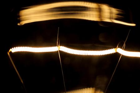 Tungsten filament in an incandescent lamp, macro photo Stock Photo