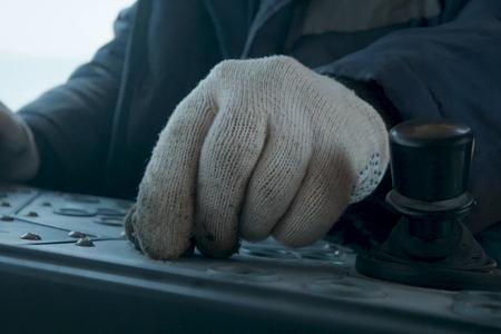 Ręka pracownika na panelu sterowania. Zarządzanie wyposażeniem w miejscu pracy.