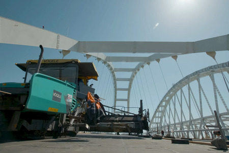 Taman, Russia - April 4, 2018: The construction of the Crimean bridge. Asphalt paving. Road works on the bridge.