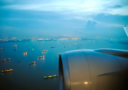 Flight of the aircraft over the port, visible ships on the water. The view from the window of a passenger plane during the flight, the wing of the turbine engine of the aircraft. Zdjęcie Seryjne