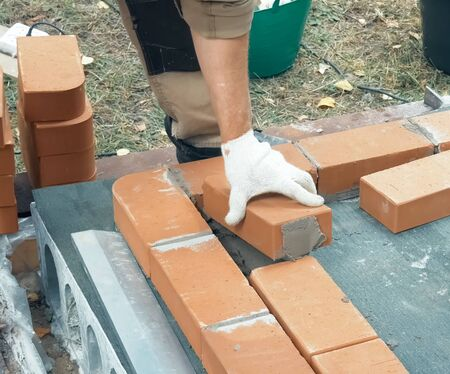 A man builds a brick wall. Brick put on the solution. Construction of a brick house.