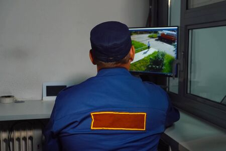 A security guard sits at the MONITOR of the CCTV camera.