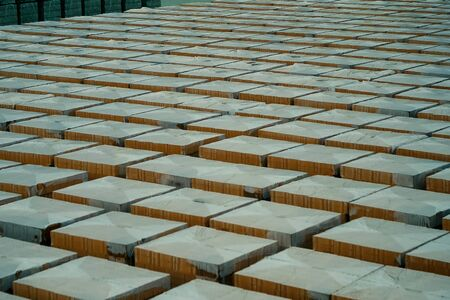 Bricks are stored in an open-air warehouse. Red brick in pallets.