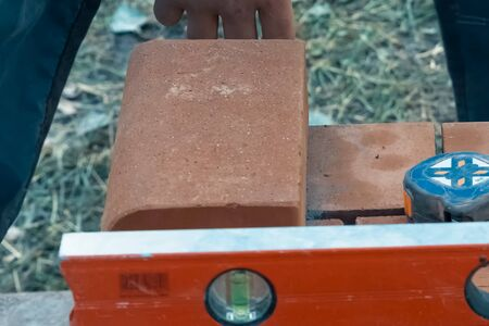 Measuring and marking bricks during the construction of the house. Standard-Bild - 140766595