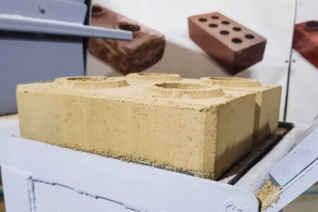 Brick making by hand pressing in a clamping mechanism.