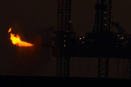 Drilling platform in the port. Oil platform at sunset with a burning torch. Towing of the oil platform.