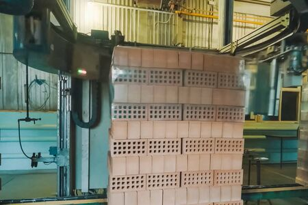 Wrapping a transport film of a brick pallet. Brick production, hollow ceramic bricks factory. Brick production, bricks factory.