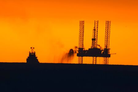 Drilling platform in the port. Oil platform at sunset with a burning torch. Towing of the oil platform. Banque d'images