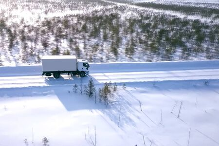 A lorry with a wagon rides along the road in winter. Winter road for a truck.