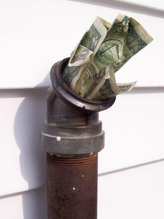 money shoved into an oil fill pipe Banco de Imagens