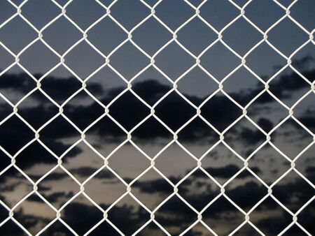 Chain link fence with dark sky photo