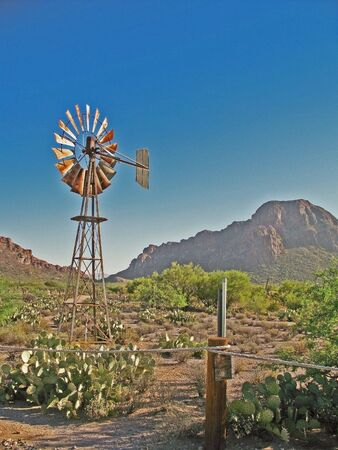 Rustic steel windmill in desert landscape Stock Photo