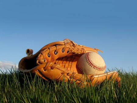 Baseball and glove resting in green grass Stock Photo