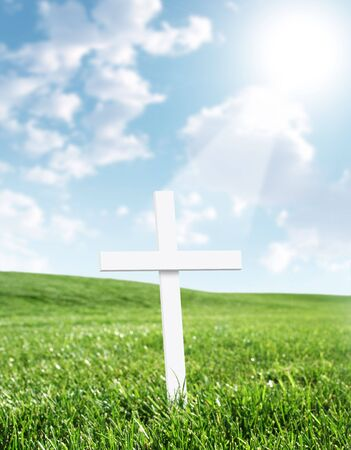 White cross in grass field with heavenly beam of light