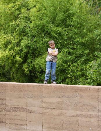 rebeldia: Chico joven con expresión de defensa de pie en pared