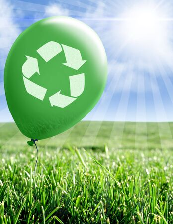 Green balloon with recycle symbol floating over green grass