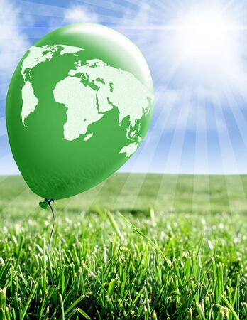 World map on green balloon floating over green grass