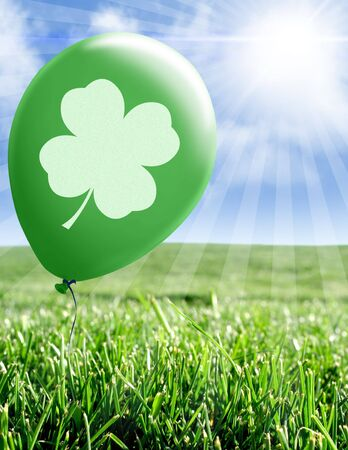 Four leaf clover on green balloon in green field photo