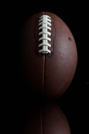 Dramatic footballl up close on black