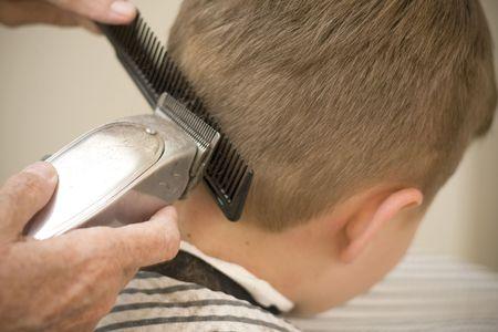 barber shop: Met behulp van tondeuse op jonge jongen de kapper
