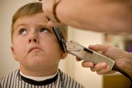 Young boy waiting for his hair cut to be over photo