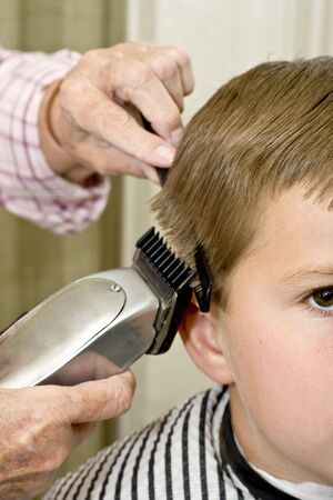 haircut: Young boy getting his hair cut clippers tapering the sides of head