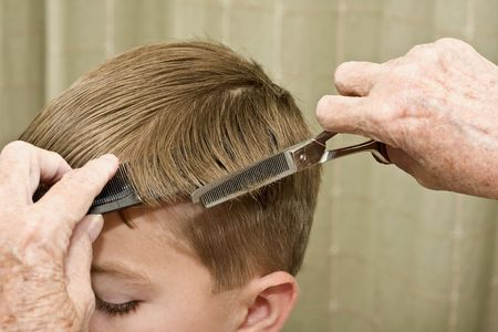 haircut: Thinning shears being used on the side of a little boys head during haircut
