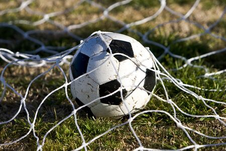 Soccer ball resting underneath the goal net Stock Photo