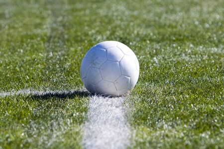 Solid white soccer ball resting on the sports field