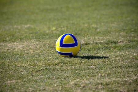 Blue & gold soccer ball resting on the field Stock Photo