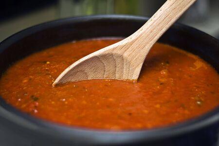 Stirring a large pot of spaghetti sauce