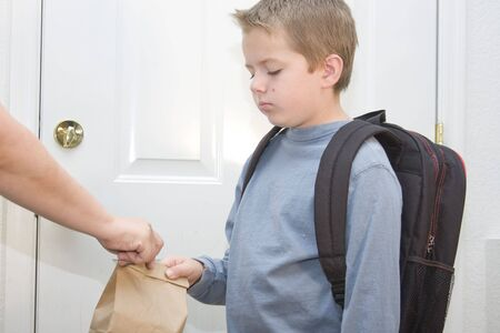 first day: Young boy unhappy about going back to school Stock Photo