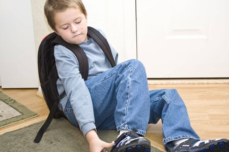 Young boy getting his shoes on, ready to go back to school photo