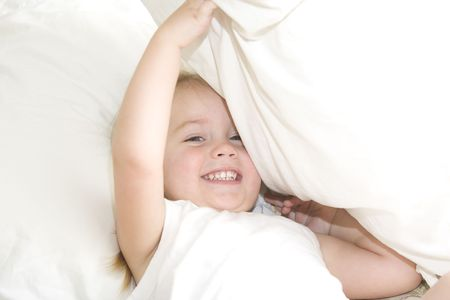 Baby girl peeking out from under a pillow Stock Photo