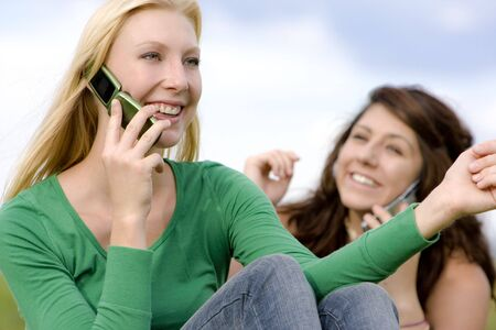 Two young ladies on cell phone conversations Stock Photo - 5234928
