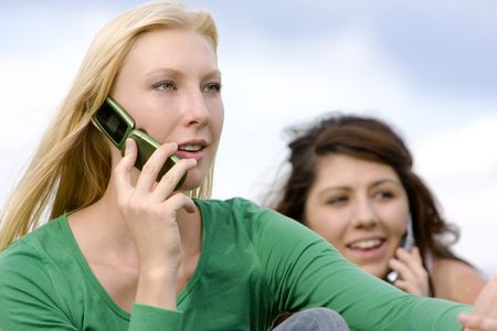 Two young ladies on cell phone conversations photo